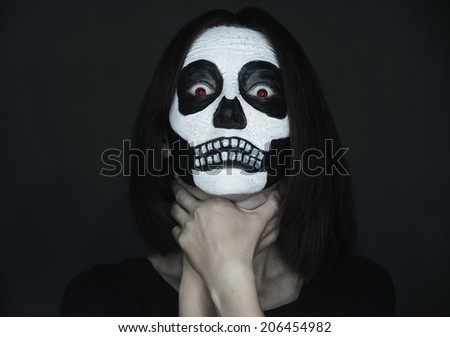 Scary woman with skull make-up choking herself on black background. Halloween face art