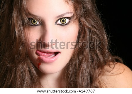 Scary woman with wolf eyes licking her lips - stock photo