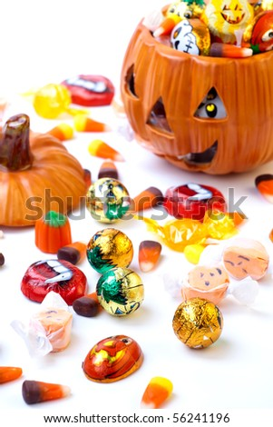 Scatter Halloween candies and orange pumpkin filled by them - stock photo