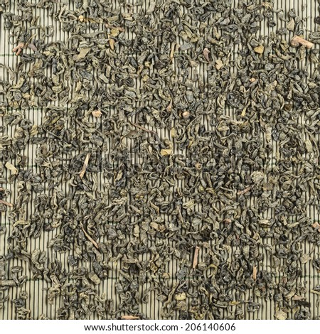 Scattered black tea over bamboo mat as abstract background top view