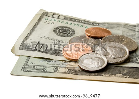 Scattered coins atop ten and twenty dollar US bills. - stock photo