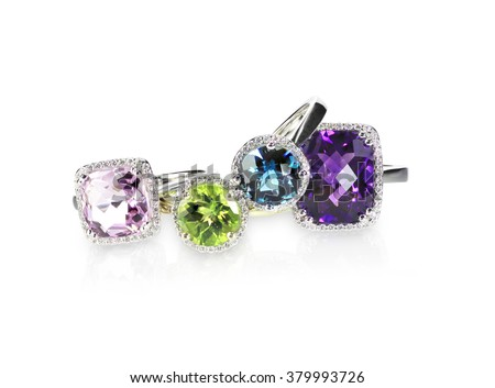 Scattered gemstone and diamond halo fine jewelry rings in a grouping - stock photo