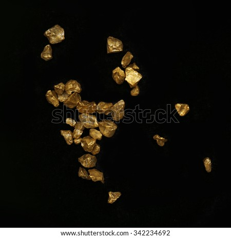 Scattered gold nugget grains, on black background - stock photo