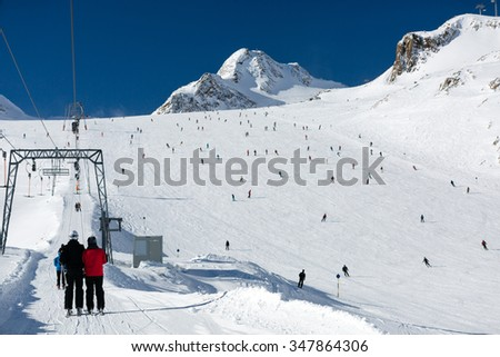 Scattered groups of skiers descend a wide ski run at the Tiefenbach glacier at the Austrian ski resort Soelden. - stock photo