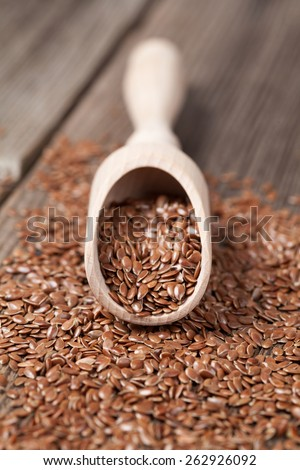 Scattered heathy little brown flax seeds nutrition on wooden background - stock photo