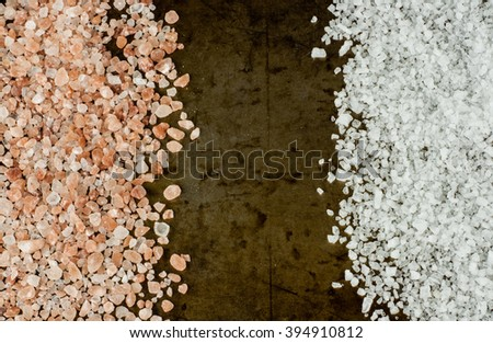 Scattered Himalayan pink salt crystals vs white salt crystals on rusty metal background, space for text - stock photo