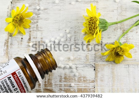 scattered homeopathic arnica pills on wooden background - stock photo