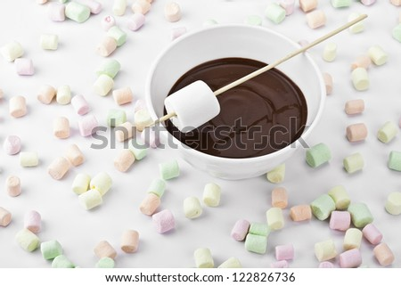Scattered marshmallows with bowl of chocolate syrup - stock photo