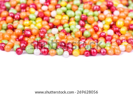 Scattered multicolored small round candies on white - stock photo