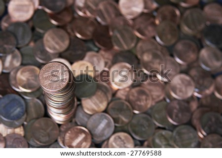Scattered pennies with one large stack of pennies.