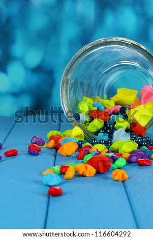 Scattered pieces of paper and colored stones with dreams in glass vase on blue wooden table on blue background - stock photo