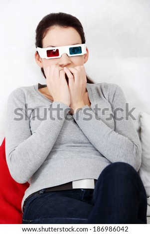 Sceared woman in 3d glasses is watching movie. - stock photo