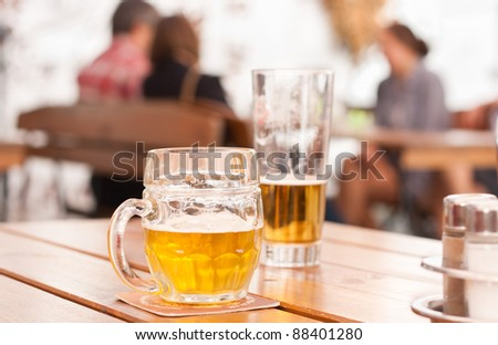 Scene from a city restaurant outdoor area: close-up of a half-filled beer mug on a wooden table - stock photo