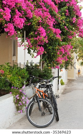 Scene from a narrow alley from a Greek island village, showing two bicycles leaning against a house covered in colorful flowers - stock photo