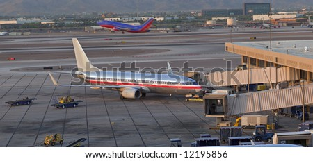 Scene from airport, plane at gate and plane taking off in background. - stock photo