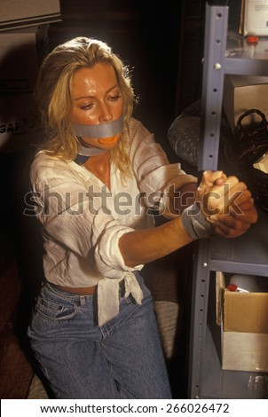 Scene from set of 'Temptation' with actress bound ang gagged, feature film, Miami, FL - stock photo