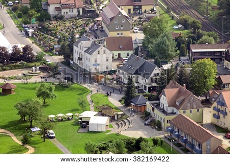 Scene of rural life: the house on a background of trees and parked cars and people. View from above