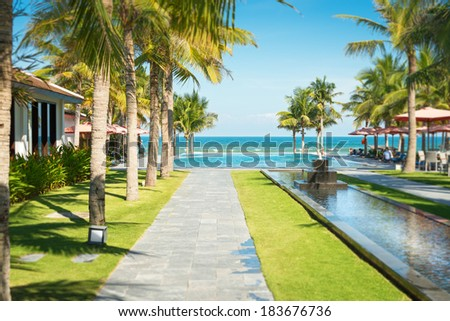 Scene of tropical resort in Vietnam. Beautiful alley with palm trees standing in rows, long water line with small stone fountain and paved paths leading to swimming pool and sea. Summer vacation. - stock photo