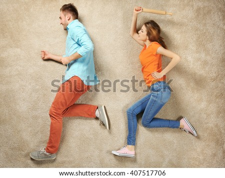 Scene simulation, woman catching up with man and trying to beat him with a rolling pin - stock photo