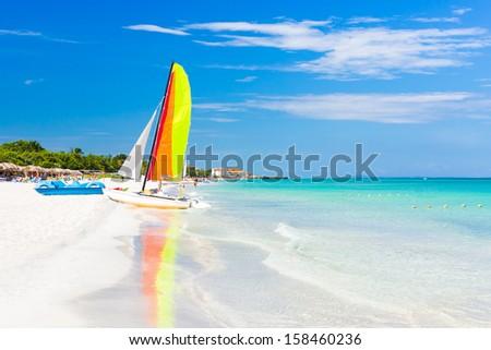 Scene with sailing boat at the famous Varadero beach , Caribbean sea in Cuba - stock photo
