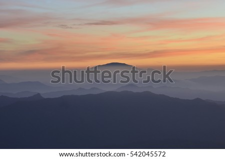 Scenery background of the view of orange sky with the mountain silhouette in the time of sunset or sun rise at the top of chiang daw mountain in chiang mai city thailand