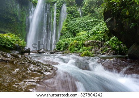 Scenery of a waterfall in green rain-forest and streaming water in Lombok, Indonesia - stock photo