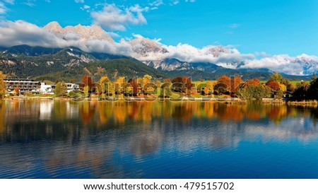 Scenery of beautiful Lake Ritzensee on a sunny autumn day in Saalfelden, Salzburger Land, Austria, with reflections of colorful fall foliage on the peaceful lake & majestic Austrian Alps in background
