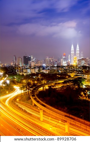 Scenery of Kuala Lumpur twin towers with stunning light trail from the busy highway traffic. - stock photo