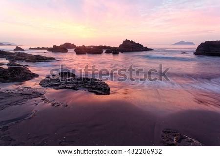 Scenery of rosy sunrise sky illuminating the sea waves of the rocky beach at Wai'ao Coast, Yilan (Ilan), Taiwan ~ A beautiful beach near Taipei City in north-east Taiwan under dramatic dawning sky - stock photo