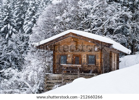 Scenery of small wood chalet over  snow covered trees on slope of Austrian ski resort. - stock photo