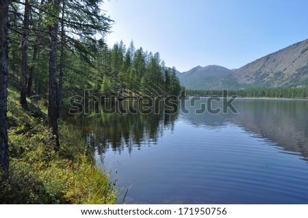 Scenery of the lake and reflections of the mountains. Russia, Yakutia, Oymyakon highlands, a ridge of Suntar-khayata, river Suntar. - stock photo