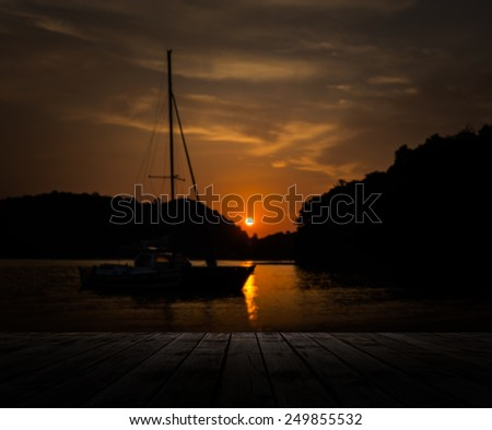 Scenery of wooden pier with sailboat and dramatic sky sunset, Phuket, Thailand, blur  - stock photo