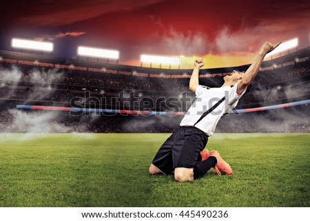 scenes from a soccer or football game with a male cheering player - stock photo