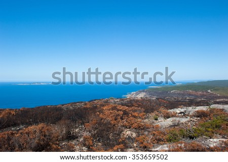 Scenic aerial panoramic view along coast of Torndirrup National Park, Albany, Western Australia, burnt vegetation, Southern Ocean, blue sky, copy space. - stock photo