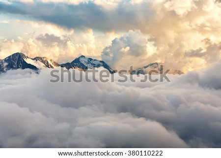 scenic alpine landscape with peaks covered by snow and clouds. natural mountain background - stock photo