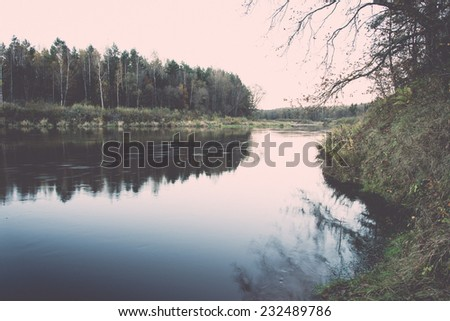 scenic autumn colored river in country with trees and reflections. Vintage photography effect.