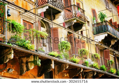 Scenic balconies of old house decorated with flowers in pots, Verona, Italy. Verona is a popular tourist destination of Europe. - stock photo