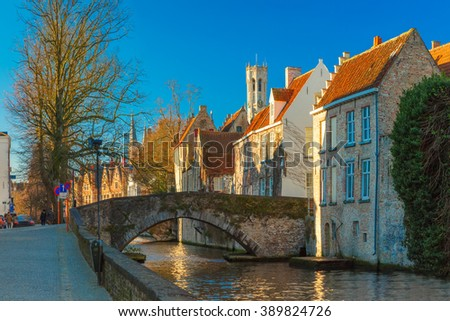 Scenic cityscape with a medieval tower Belfort, bridge and the Green canal, Groenerei, in Bruges in the morning, golden hour, Belgium - stock photo