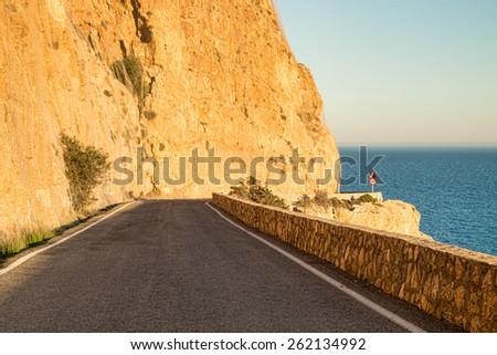 Scenic coastal road running along a rocky coastline - stock photo