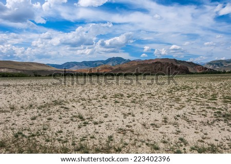 Scenic desert steppe landscape with mountains. Dry land with rare plants as foreground and mountains, blue sky and clouds in the background.