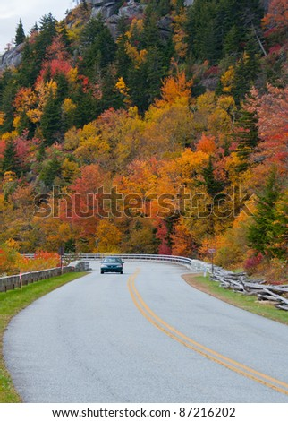 Scenic drive. A car, surrounded by colorful fall foliage,  travels the scenic Blue Ridge Parkway, North Carolina. - stock photo