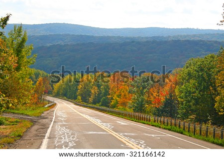 Scenic drive through autumn trees - stock photo