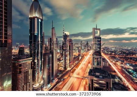 Scenic Dubai downtown architecture in the evening. Rooftop skyline with Sheikh Zayed road and many illuminated towers.