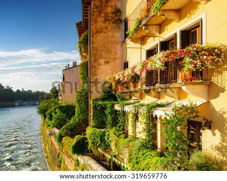 Scenic facades of old houses decorated with flowers on waterfront of the Adige River in Verona (Italy) in morning sun. Verona is a popular tourist destination of Europe. - stock photo