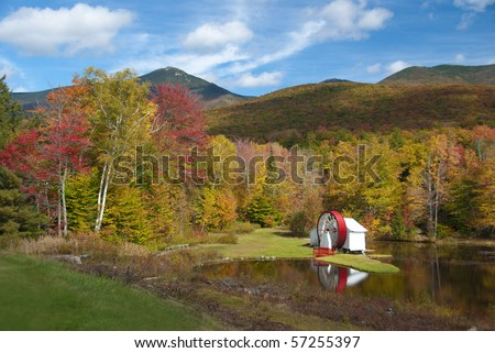 Scenic fall view of New Hampshire water mill on pond - stock photo