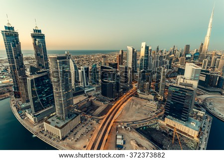 Scenic fisheye view of Dubai's business bay towers at sunset. Fantastic rooftop skyline. - stock photo