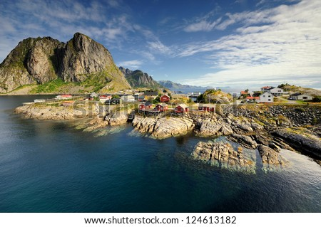 Scenic fjord on Lofoten islands, with typical red fishing hut and towering mountain peaks, Sakrisoy, Norway - stock photo