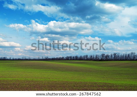Scenic green field with hills and bright dramatic cloudscape - stock photo