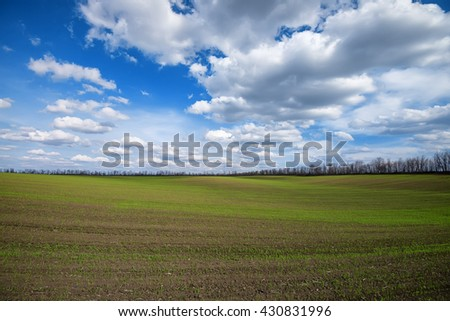 Scenic green field with hills and bright dramatic cloudscape