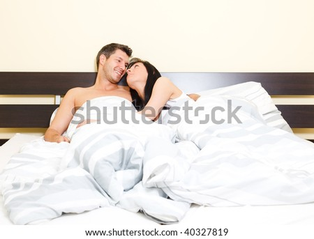 Scenic in bedroom of pair of loving young couple lying in bed looking eachother romantic while cuddling and embracing - stock photo